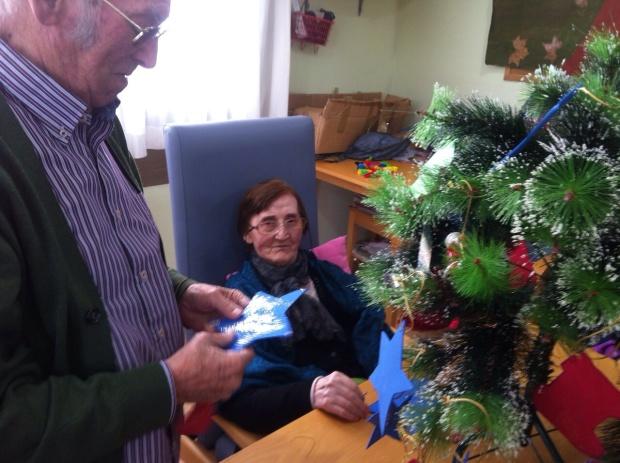 Martina mira y sonríe mientras Manuel añade una estrella al árbol